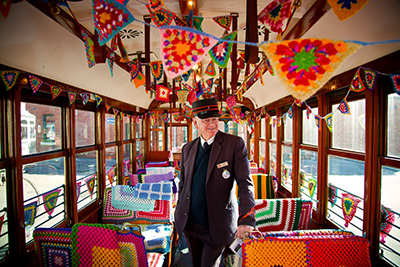 Tram Conductor standing aboard the Yarn Bomb Tram surrounded by crochet