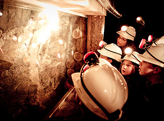 A group of children looking at gold in the quartz underground at Central Deborah Gold Mine
