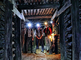 Four Central Deborah Gold Mine Tours standing in an underground tunnel with timber cladding