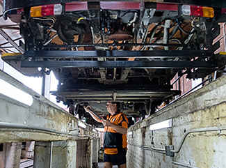 Maintenance worker in a tram pit restoring a Bendigo tram