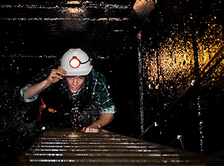Visitor climbing ladders in the shaft at Central Deborah Gold Mine