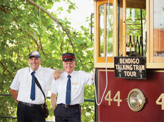 Two Tram Drivers standing next to a burgundy Vintage Talking Tram