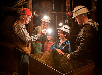 Tour Guide showing a family a gold nugget on an underground Mine Experience Tour at Central Deborah Gold Mine